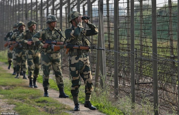 India's Border Security Force (BSF) soldiers patrol along the fenced border with Pakistan in Ranbir Singh Pura sector near Jammu on Tuesday